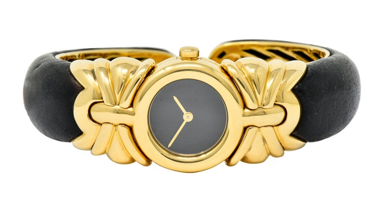 Centering a round sapphire crystal cover over a black watch face and polished gold hands  Surrounded by a polished gold circular bezel with gold crown  Flanked by stylized gold shoulders that complete as a black leather cuff  Cuff is backed by