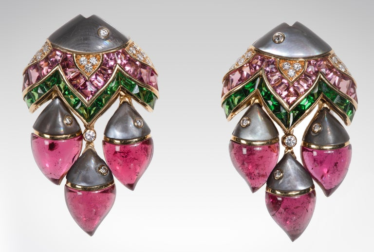 Illustrating Bulgari's mastery of design and craftsmanship, these ear clips are exceptionally unique and spectacular. Each piece is designed as a school of stylized fish set with pink tourmalines, tsavorite garnets, grey mother of pearl, and