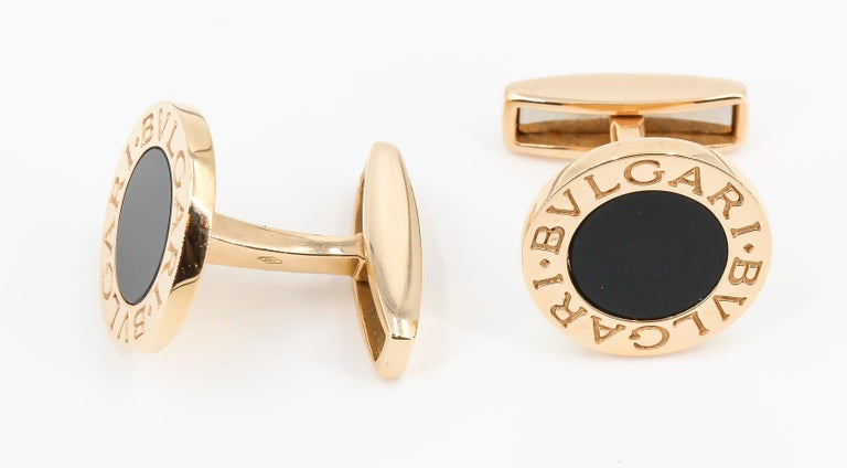 Handsome inlaid onyx and 18K yellow gold round cufflinks by Bulgari. They feature black onyx inlays in the middle over an 18K gold setting with