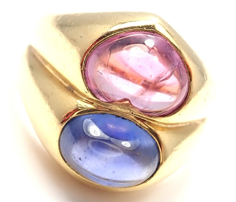 18k Yellow Gold Pink & Blue Sapphire Ring By Bulgari.  With 1 Oval Shaped Blue Sapphires  And Heart Shaped Pink Sapphire 5mm x 8mm Pink Sapphire 2.30ct Blue Sapphire 2.11ct Details: Size: 5.5 (Resize Available) Weight: 14.4 grams Width: 15mm Stamped