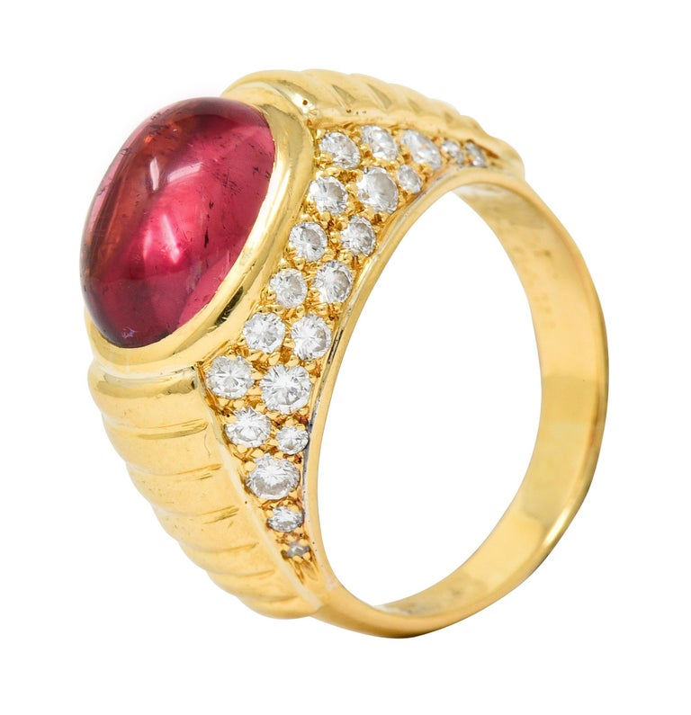 Band ring centers an oval tourmaline cabochon measuring approximately 11.0 x 8.0 mm  A deeply saturated pink, transparent with subtle natural inclusions  Accented North and South by pavé set round brilliant cut diamonds weighing in total