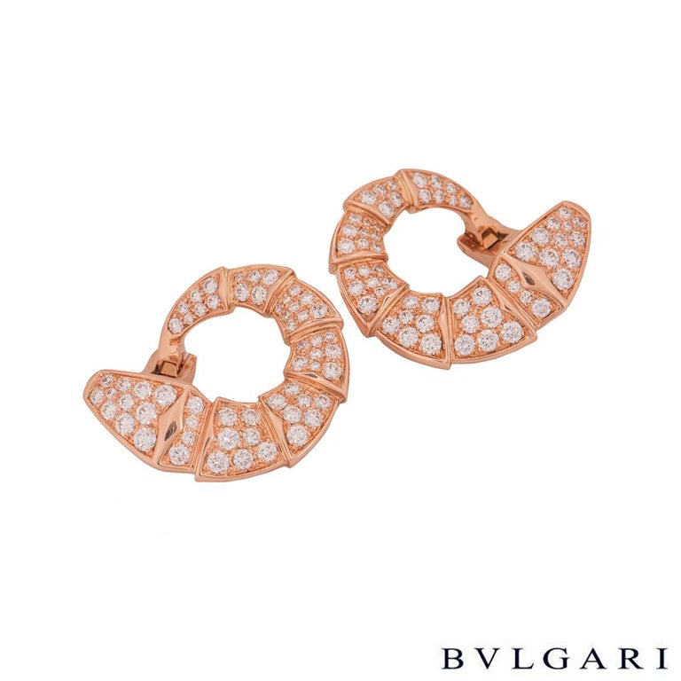 An 18k rose gold pair of diamond earrings by Bvlgari from the Serpenti collection. The earrings are in the shape of the iconic Bvlgari Serpenti snake set with pave round brilliant cut diamonds throughout the intersected body. There are 114 round