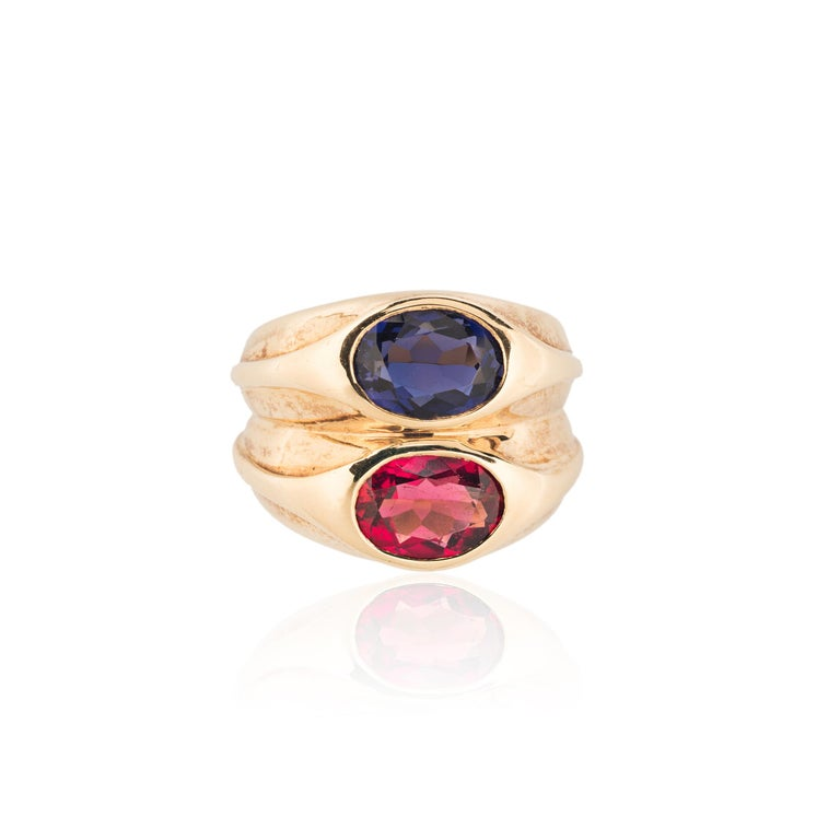 Bulgari's deft color sense is on full display in their iconic Doppio rings. This version features a vibrant oval ruby paired with a deep blue sapphire.  - 18k yellow gold - Oval ruby approximately 1.87 carats - Oval sapphire approximately 1.94
