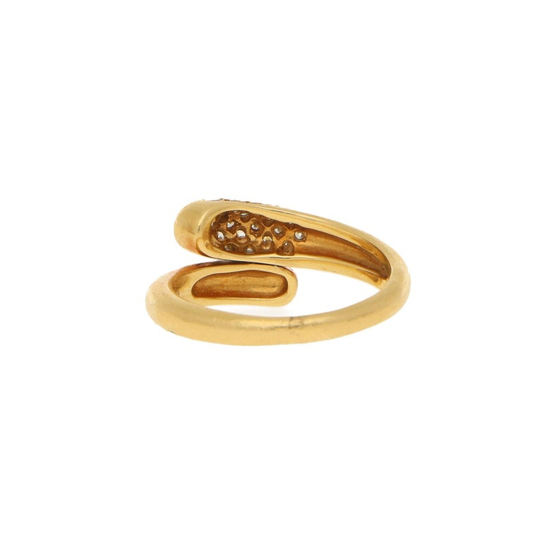 A vintage Bvlgari Serpenti ring in a crossover design set in 18k yellow gold. Within the crossover design one terminal is pave set with 19 round brilliant cut diamonds, totalling an approximate weight of 0.38ct, G/H colour and VS clarity.   This