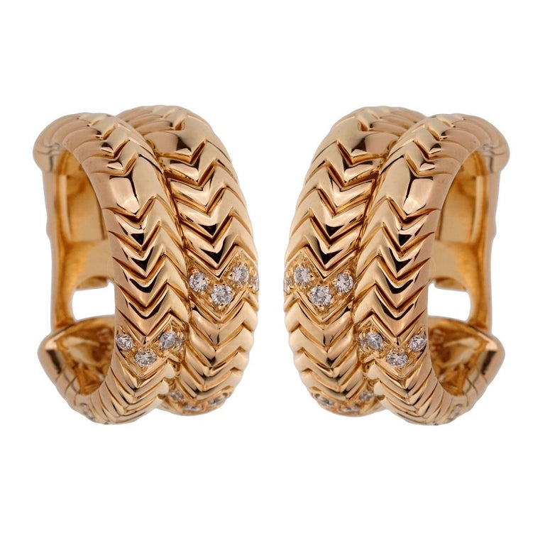 An iconic set of authentic Bulgari Spiga earrings adorned with round brilliant cut diamonds in shimmering 18k yellow gold.