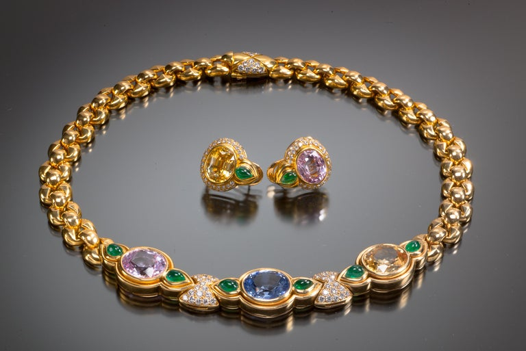 This gold link necklace is set with three large oval-shaped sapphires: one pink, one blue and one yellow. Emeralds between them appear as leaves with lively diamond accents. Necklace total sapphire weight is 31.88 carats. Total emerald weight is