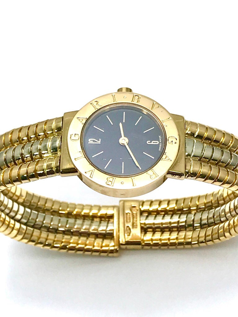 An easy to slip on Bulgari tubogas 18 kaart yellow, rose, and white gold open flex watch bangle bracelet.  The watch dial features arabic numerals at 12 and 6, with index markers as the other hour indicators.  The bezel is engraved with