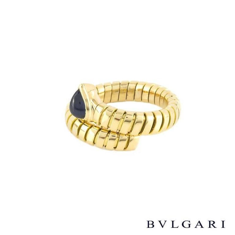 An 18k yellow gold sapphire ring from the Bvlgari Tubogas collection. The ring is features a 1.31ct pear shape cabochon sapphire, set to a flexi link serpant design band. The 5mm ring is a size P, US 7 1/2 but can be adjusted slightly larger and has