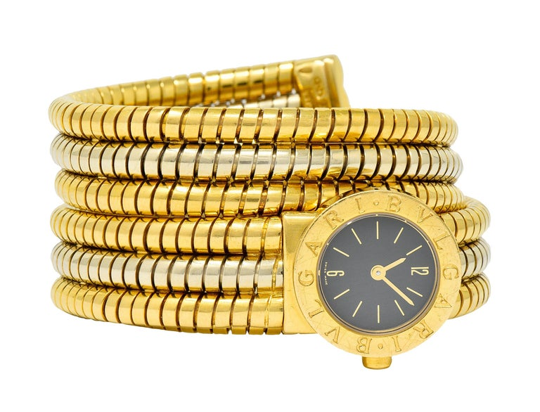 Watch is designed with a coiled tubogas watchband that adjusts to fit most wrists  Comprised of three segments of deeply ridged white and yellow gold  And features a round watch face with gold numerals and dial  Covered by sapphire crystal with a