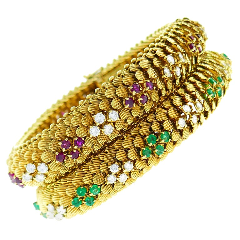 Pair of yellow-gold bracelets set with diamonds, rubies and emeralds, 1960s, offered by the Nadine Krakov Collection
