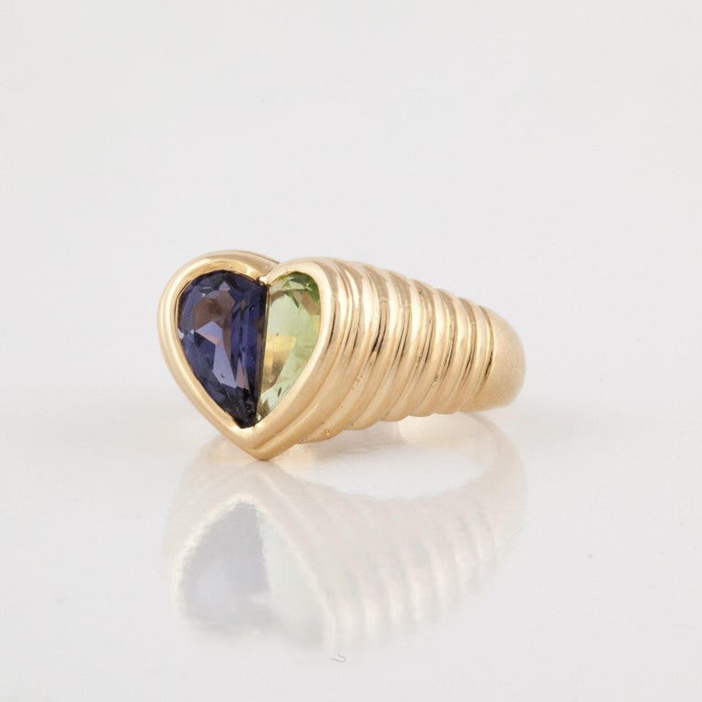 18K yellow gold ring by Bulgari.  It features a peridot and an iolite to form the heart in the center of a ridged shank.  Ring is currently a size 6.  Measures 1/2 an inch x 1/2 an inch.