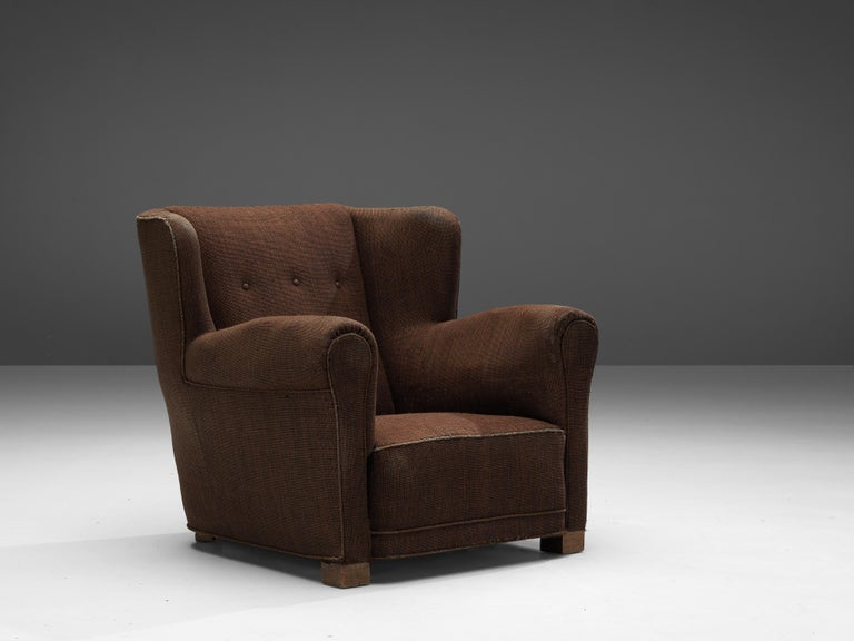 Danish lounge chair, wood, fabric, Denmark, 1950s  This bulky lounge chair features a sturdy yet inviting look. The wide seat with armrests and the backrest with wings, create a comfortable experience for the sitter. From the back, the chair has a