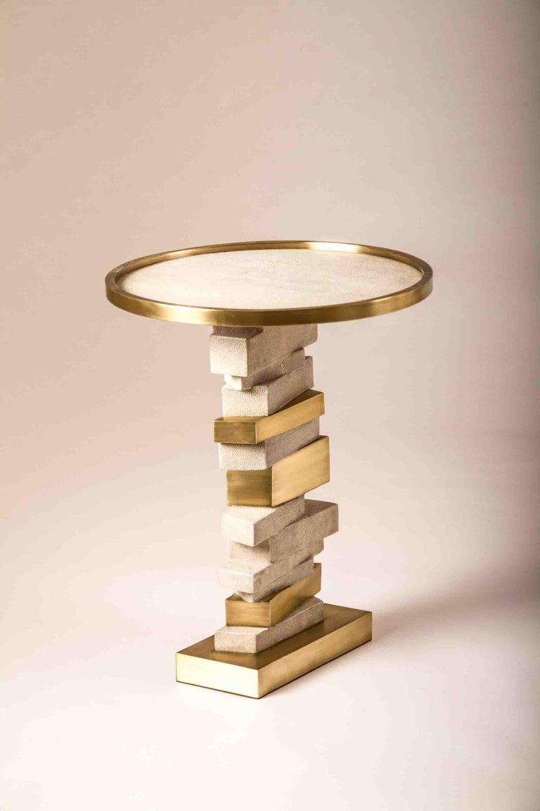 The Bullion side table is inspired by stacked gold bars. The top of the table is inlaid in cream shagreen with a bronze-patina brass frame. The stacked inspired gold bars are inlaid in a mixture of shagreen and brass. This piece makes for a playful