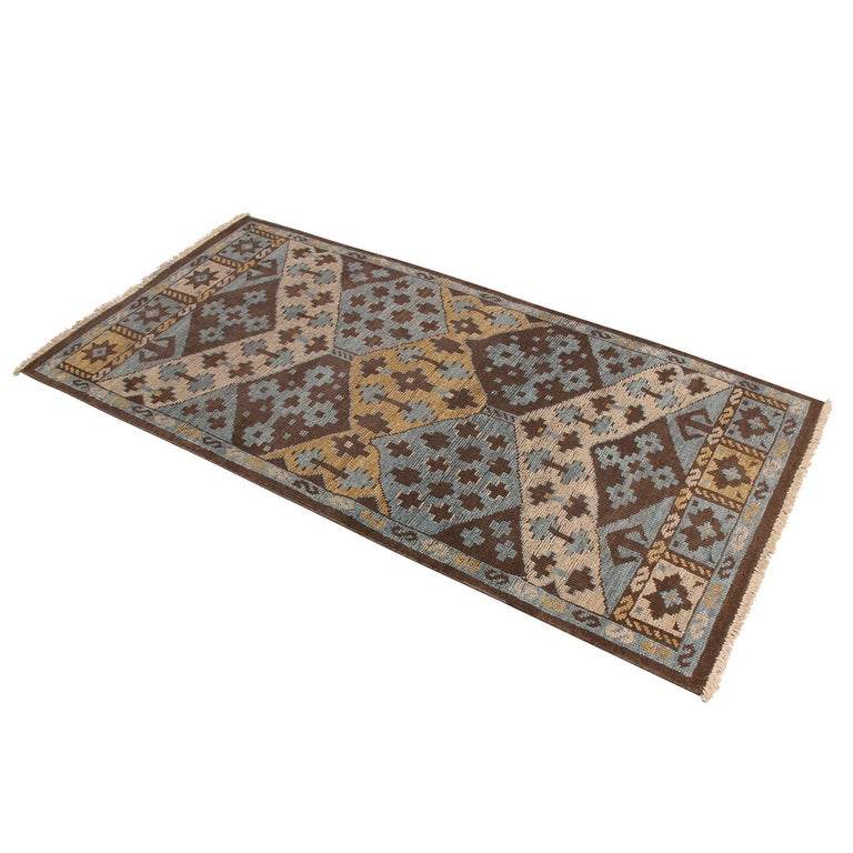 Originating from India, this hand knotted contemporary wool rug hails from Rug & Kilim's premier Burano collection, enjoying a unique marriage of tribal patterns with more forgiving, versatile hues of brown, beige, blue, and golden-yellow