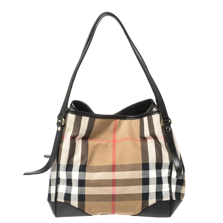 This Canterbury tote from Burberry is crafted with their signature House Check fabric and leather. It comes with a flat handle, protective metal feet, and a canvas-lined interior that can hold all your daily necessities. Simple in design, the bag is