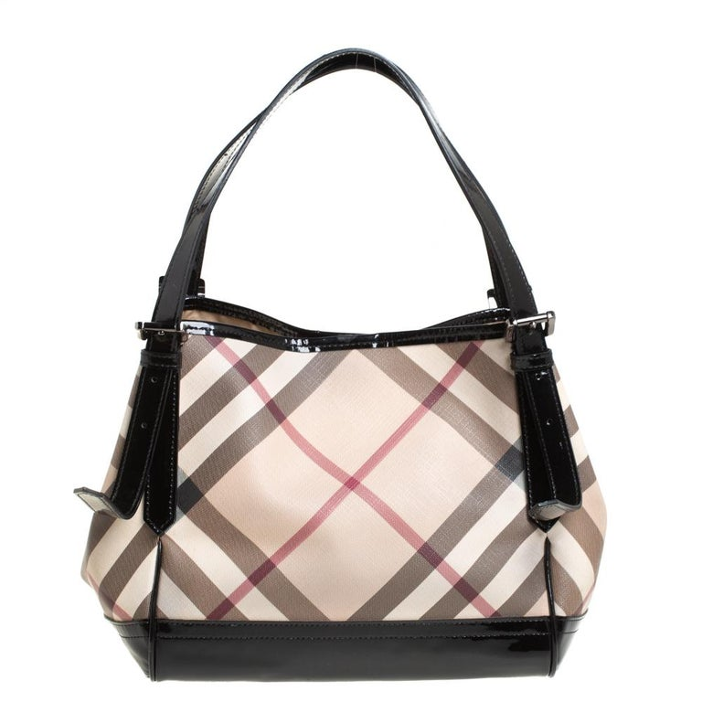 This Canterbury tote from Burberry is crafted from Nova Check PVC and enhanced with patent leather. It comes with dual flat handles, protective metal feet, and a spacious fabric-lined interior that can hold all your daily necessities. Simple in