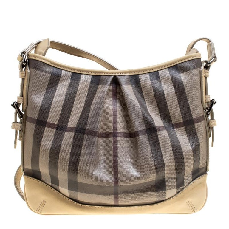 Complete a stylish look with this beautiful Burberry bag. It has been wonderfully crafted from Smoke Check PVC and designed with leather trims and a zipper leading to a spacious canvas interior. This crossbody bag is completed with a leather