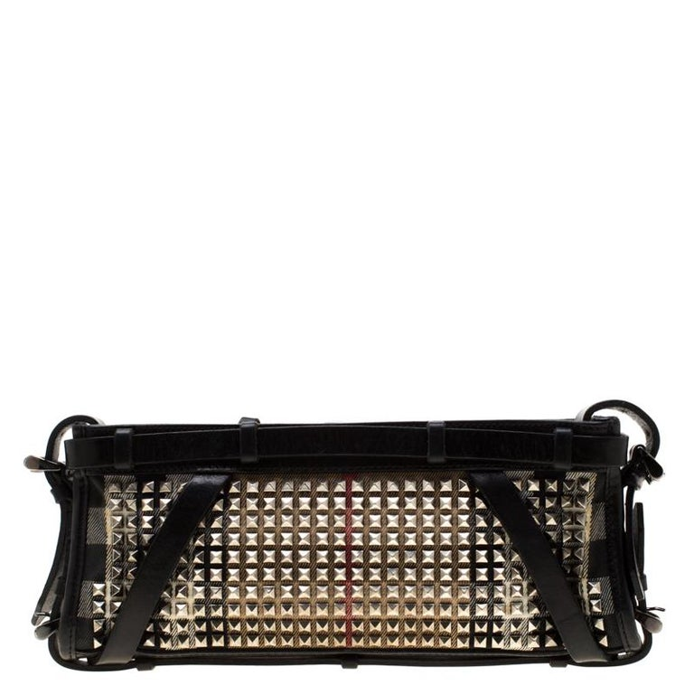 Crafted from signature house check canvas and styled with gold-tone studs all over the exterior, this Burberry clutch is that handy accessory that you'll love to carry for parties and evening outings. It features buckled straps at the front and all