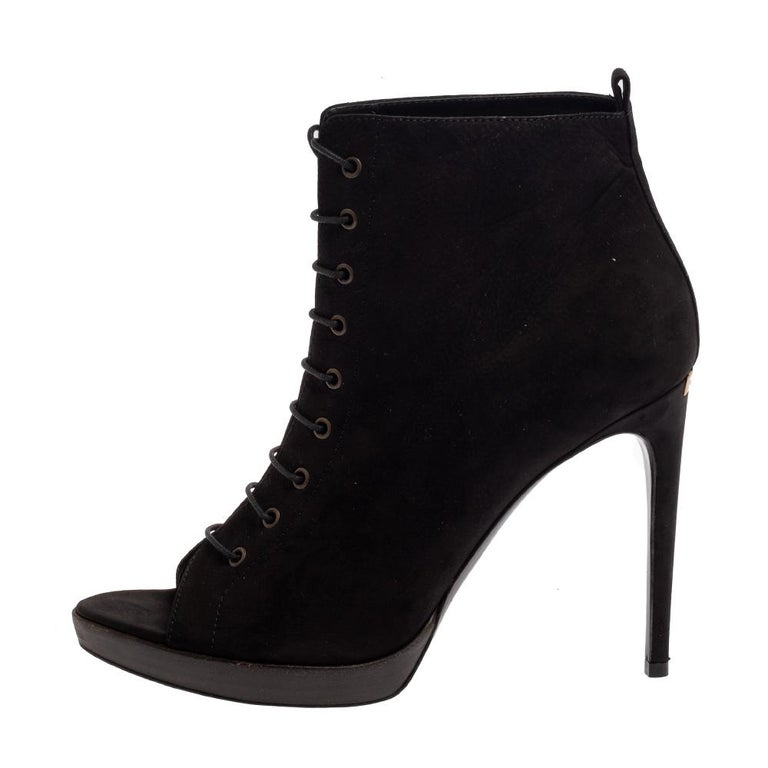 These ankle booties from Burberry have been designed to present a fashion-forward appeal. The peep-toe booties are covered in black suede and designed with lace-ups along the front and 12 cm slim high heels.  Includes:Original Box, Extra Heel Tip