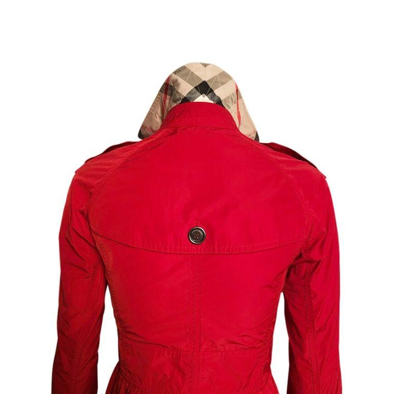 The cutest Burberry Brit fire engine red mini trench coat. This stirking coat features Burberry Britt gunmetal buttons and hardware, classic Burberry check print fabric in upper back interior and underneath collar, and gorgeous peplum cut.