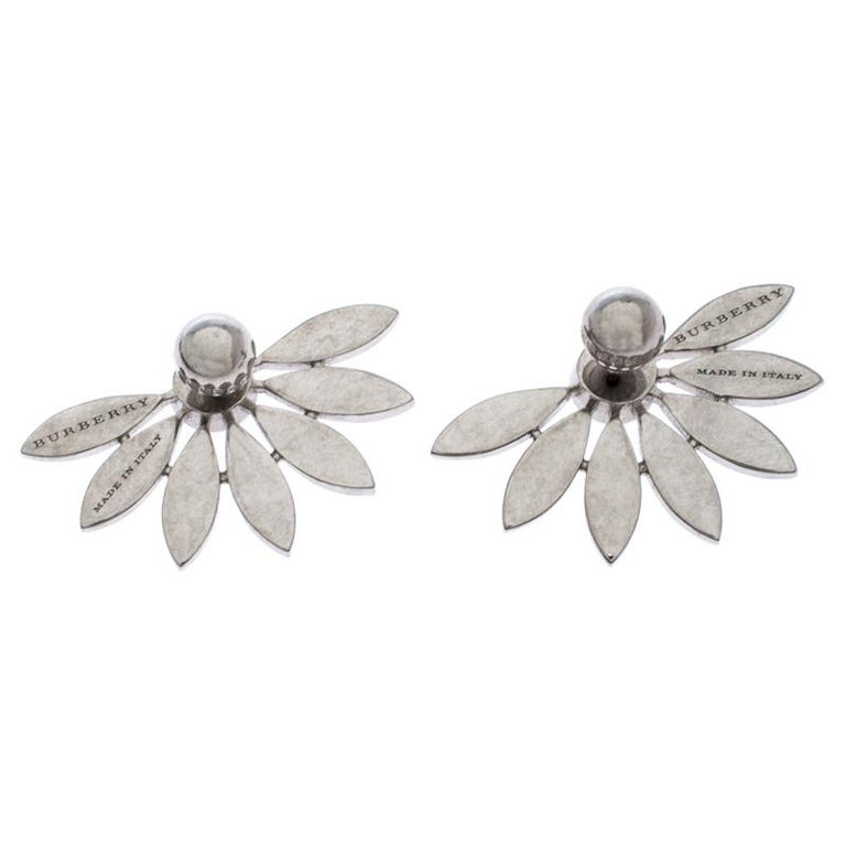 These earrings from Burberry tugs at one's heartstrings in the sweetest way. Sculpted from silver-tone metal and lit by crystals, the pair comes as daisies cut in half. Be sure to try them with black dresses and swept hair.  Includes: Original