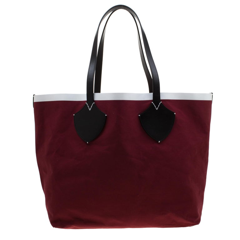 Crafted by Burberry, the giant canvas and leather tote comes in dual tones of black and maroon. This Archive logo bag features a wide canvas interior for you to house more than just your essentials. Designed with two top handles, the creation will