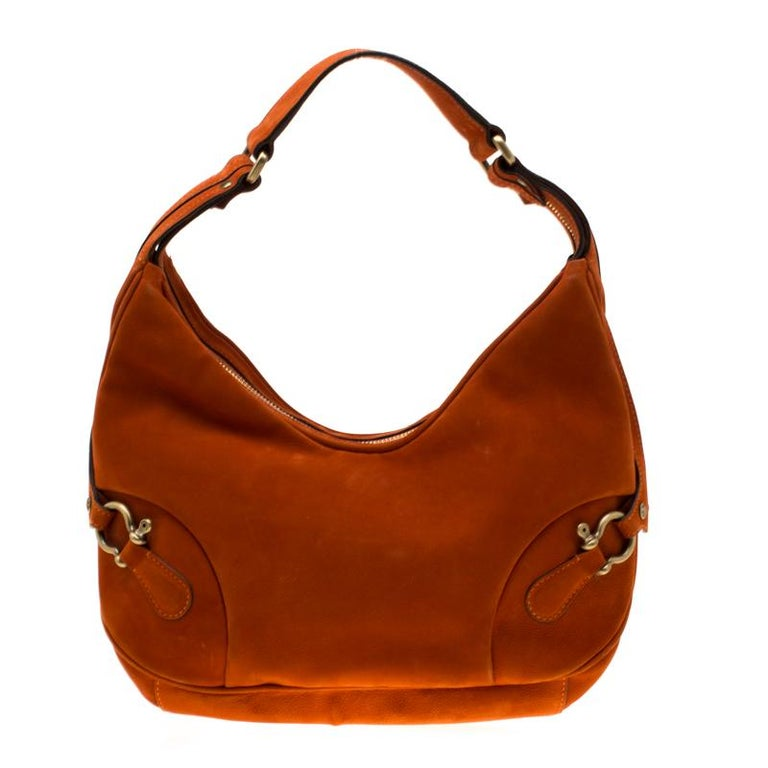 This strikingly stylish leather bag does dual work as a fashion accessory and practical necessity. The interior is lined with fine canvas to give it a mix of style and durability. This orange hobo is designed with buckle trims on the front and back.