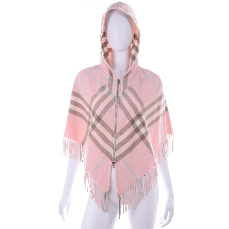 This is a pretty Pink Plaid Burberry poncho with a hood. Cropped style so can fit up to a size Medium and it has a metal zipper down the center front with a bottom zipper that can be worn open from the bottom.  Made in Scotland. of 90% Merino Wool