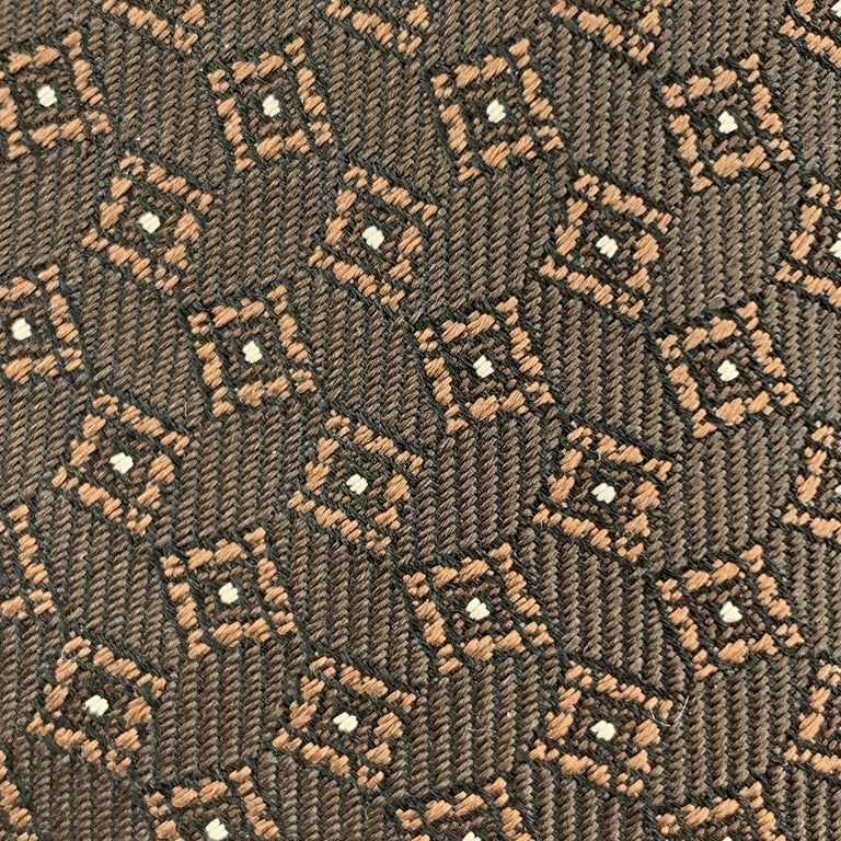 BURBERRY PRORSUM skinny tie comes in brown silk twill with all over copper textured square print. Made in Italy.  Excellent Pre-Owned Condition.  Width: 2 in.