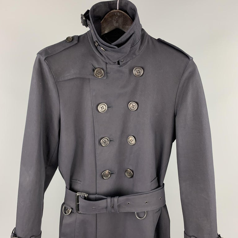 BURBERRY PRORSUM trench coat comes in a navy cotton with a full black monogram print liner featuring a belted style, high collar design, epaulettes, belted sleeve details, hook & eye, back vent, and a double breasted closure. Comes with dust bag.
