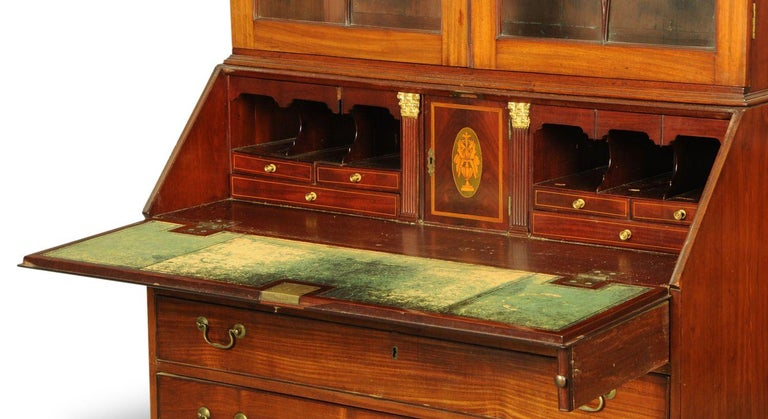 A George III mahogany bureau bookcase, with swan neck pediment above a pair of glazed doors with circular wooden astragals, satinwood banded fall front opening to a fitted interior and with four long graduated oak lined drawers with brass swans neck