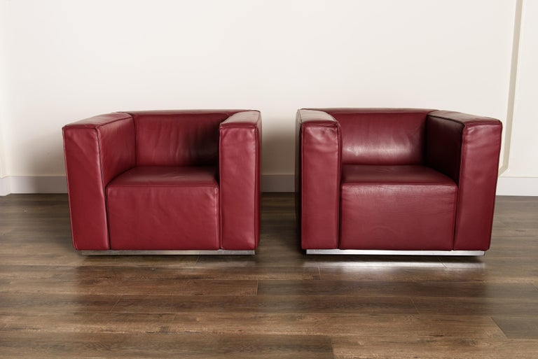 This incredible pair of 'Blox' club chairs by Jehs + Laub for Cassina are upholstered in high quality thick burgundy leather with a heavy steel frame and base wrapped in chrome. Highly comfortable, these leather club chairs can dress up any room