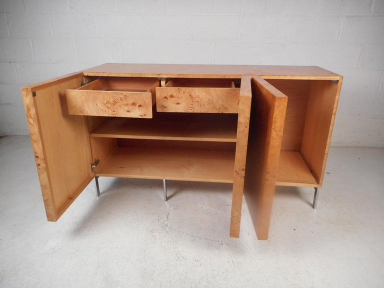Stunning midcentury credenza in the style of Milo Baughman. Burl maple adorns the entirety of the piece's exterior. Supported by stylish chrome base. Two cabinets with drawers and shelving offer ample storage space. This piece is sure to make a
