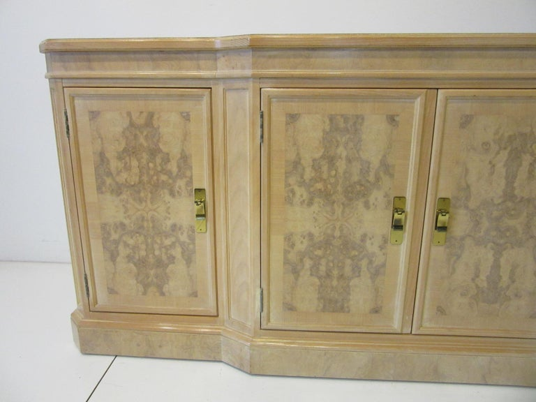 A very well crafted bookmatched olive and ashwood server cabinet, two doors to each end with adjustable shelve and two center double doors having three drawers all with heavy brass pulls. Retains the manufactures label to the drawer by the Heritage