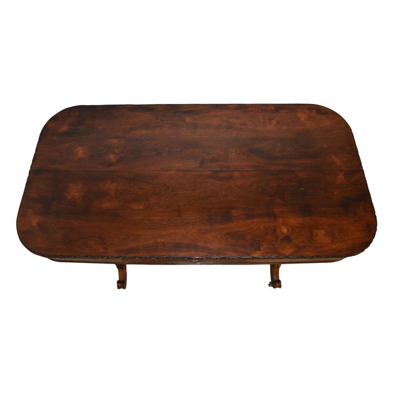 Featuring a beautiful burled, veneer top over oak with rounded corners and a carved edge, this table is raised on two mahogany turned legs, which terminate in scrolled feet with carved flowers at their centers. A turned stretcher unites the legs,