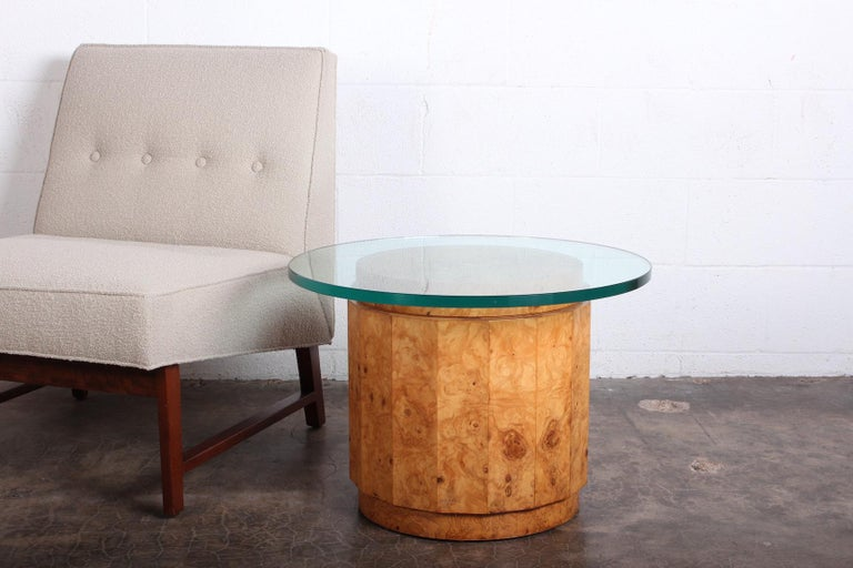 A burled olive table with original 3/4 thick glass top. Designed by Edward Wormley for Dunbar.