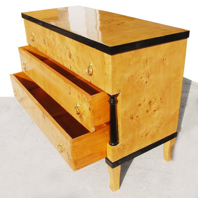 Burled wood Art Deco style dresser with ebonized trim. Three drawers and brass ring pulls.