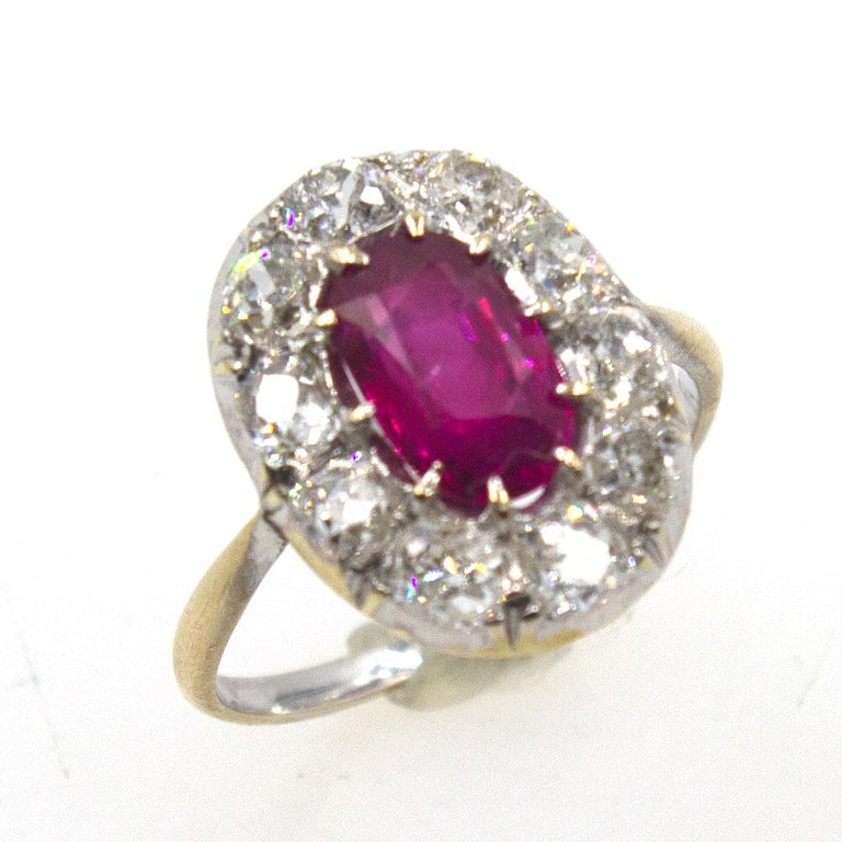 Gorgeous Burma Ruby and Diamond Antique Ring. The yellow and white 14 karat gold mounting features 10 near colorless Old Mine Cut diamonds that equal approximately 1.50 carat total weight. The diamonds surround a 9.57 x 6.18 x 3.97 mm Natural Burma