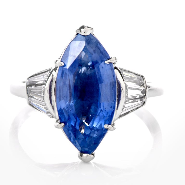 This beautiful engagement ring displays a lovely marquise inspired design and is crafted in solid Platinum. Centered with a dazzling 6.58 carat natural Burma Sapphire, prong set. It is adorned to the sides with 6 genuine tapered baguette cut