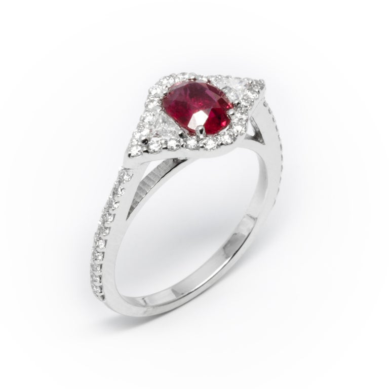 Eighteen karat white gold ruby cocktail ring surrounded two trillion diamonds and melee diamonds  Ring finger size 6.5  Diamond carat weight 0.75  Trillion diamond carat weight 0.25  Burma Ruby carat total weight 1.07 Diamond quality G VS New ring