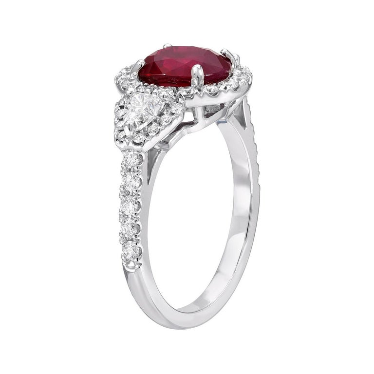 Burma Ruby oval weighing a total of 2.38 carats is surrounded by a total of 0.64 carat diamonds in this special 18K white gold cocktail or engagement ring. Size 6.25. Re-sizing is complimentary upon request.  Returns are accepted and paid by us