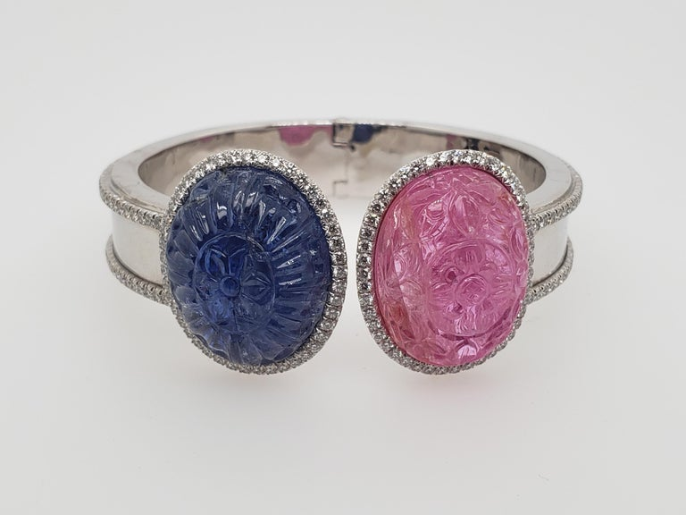 Pink & Blue Carved Cabochon Burma Sapphire & Ruby Bangle  Featuring two Oval-shaped carved with an elaborate floral pattern cabochon Pink and Blue sapphires weighing 49.81 and 46.01 carats, with AGTA Certificates Stating they are of Burma Origin,