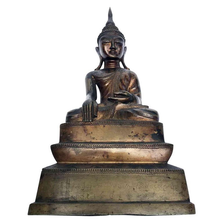 A Burmese 18th century bronze Buddha with small pointed hair locks Shwebo Thorns, on top attached with a tall flame. The eyes of this Buddha are downcast with arched eyebrows, the long ear loops and smiling lips, all expounding a serene