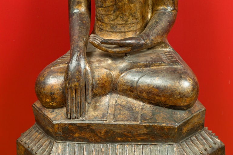 A Burmese Shan style dry lacquered and gilt wooden Buddha from the 17th century with smiling expression, seated on a pedestal. Created in Burma during the 17th century, this Shan style dry lacquered and gilt wooden statue depicts a seated Buddha in