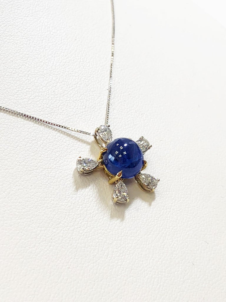 Gorgeous 5.13 ct Burmese blue sapphire cabochon round with beautiful deep blue color and bright crystal.  The blue sapphire is surrounded by good quality white diamond pear shapes in 18k white and yellow gold.  This pendant necklace is ideal for
