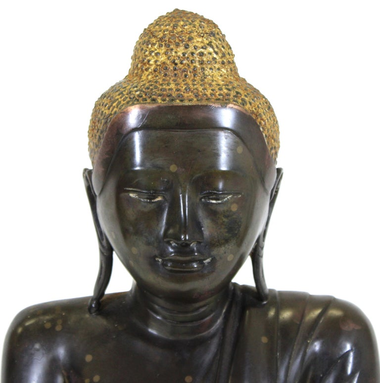 Burmese bronze sculpture of a seated Buddha with partial gilding, with his hands in bhumisparsha mudra, the gesture of calling the earth to witness, symbolizing the moment of the Buddha's enlightenment. The piece was likely made in the early 20th
