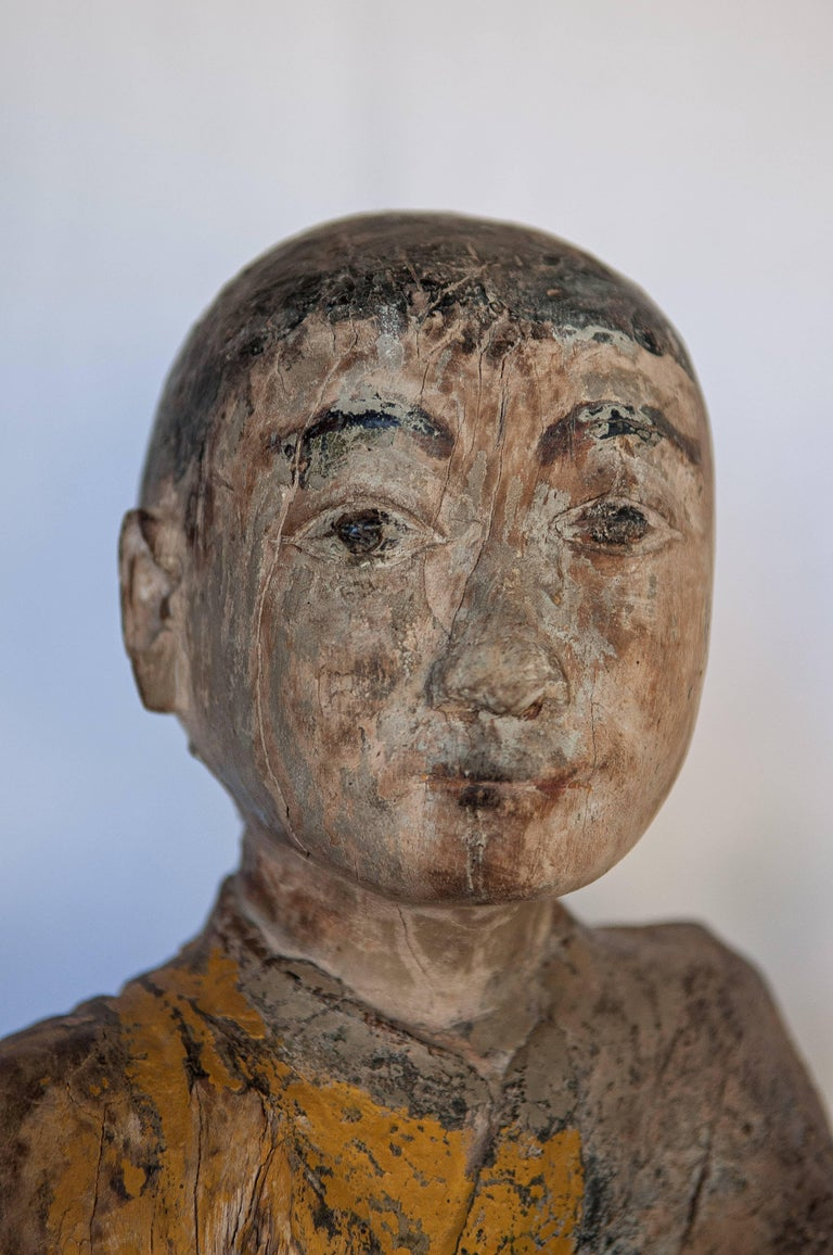 Burmese Buddhist wood carving. Sitting monk or teacher, early 20th century. This simple yet wonderfully expressive carved figure from Burma was most likely placed in a village shrine or temple. Long years of exposure have eroded the underside of the