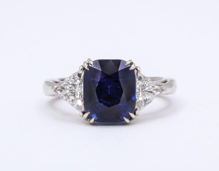 Burmese Sapphire Diamond Platinum ring. Burmese cushion cut sapphire @ 5.12 carats tw.  AGL report 1102177.   Two triangular trillion cut diamonds @ 1.50 carats   7/8 inches across diamond to diamond x 3/8 inches wide x 1/4 inches
