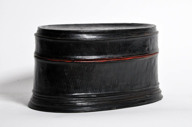 This lightweight box is made from woven rattan bonded together and sealed with red and black tree sap lacquer. It is very lightweight and break-resistant. We believe this piece is from central Burma but it could also be from the Shan States. Red