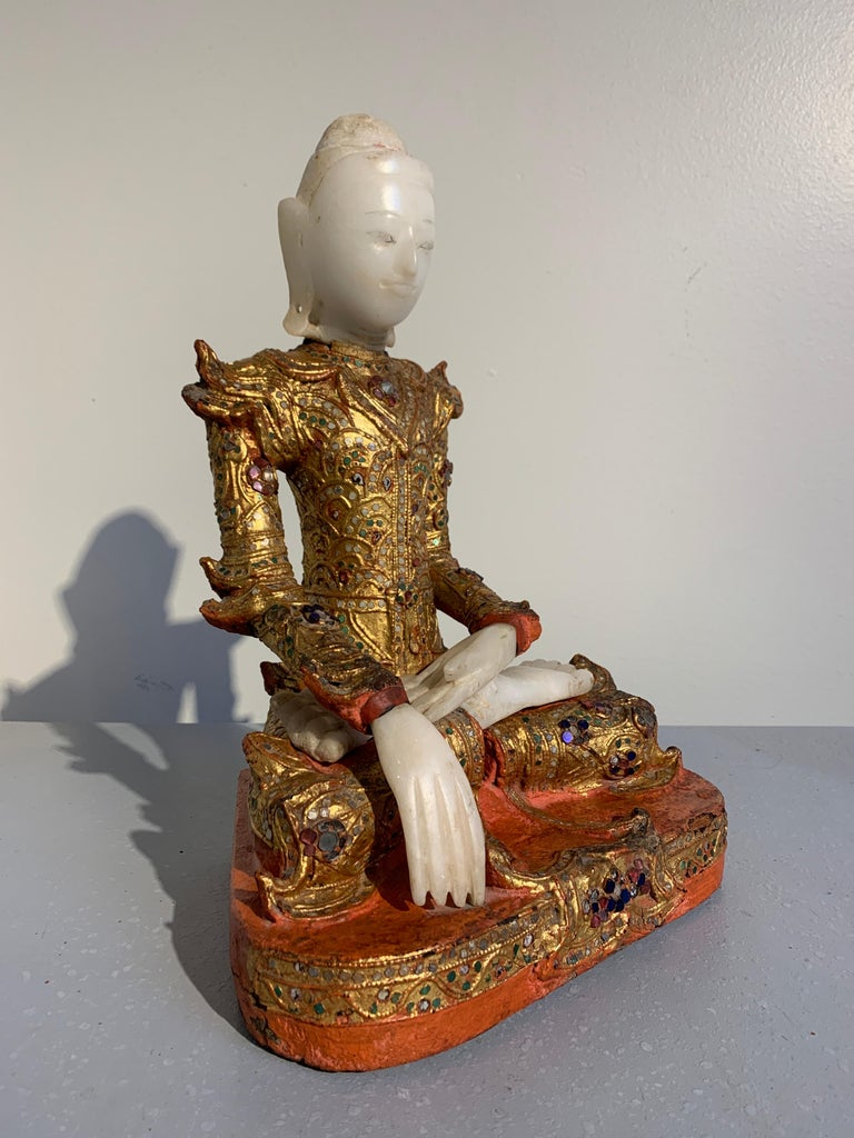 A resplendent Burmese Buddha in royal attire, known as Jambupati, carved from teak, lacquered, gilt and embellished with glass